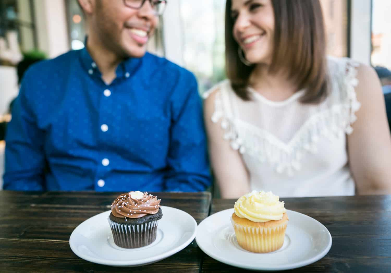 Two plates with cupcakes in front of a couple during an Astoria Park engagement shoot