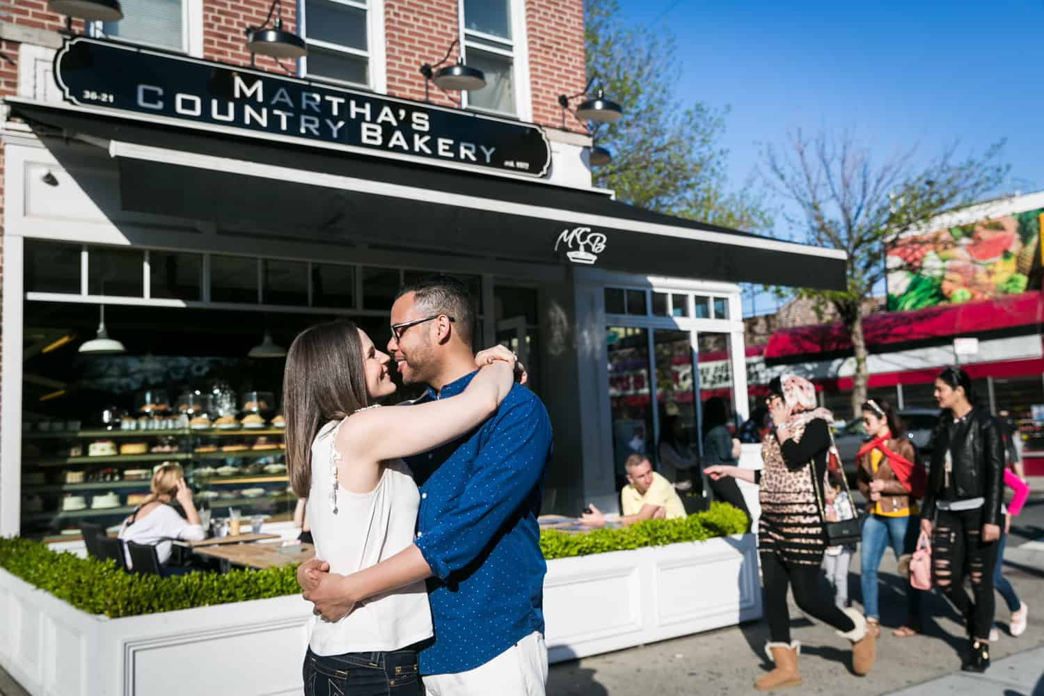 Couple kissing in front of Martha's Country Bakery in Astoria