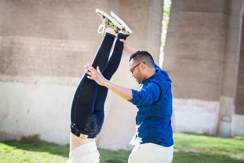 Man holding woman's legs during an Astoria Park engagement shoot
