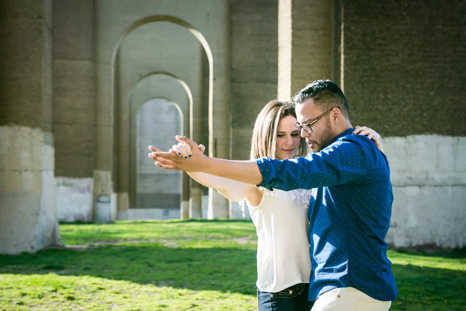 Couple dancing in front of stone arches during an Astoria Park engagement shoot