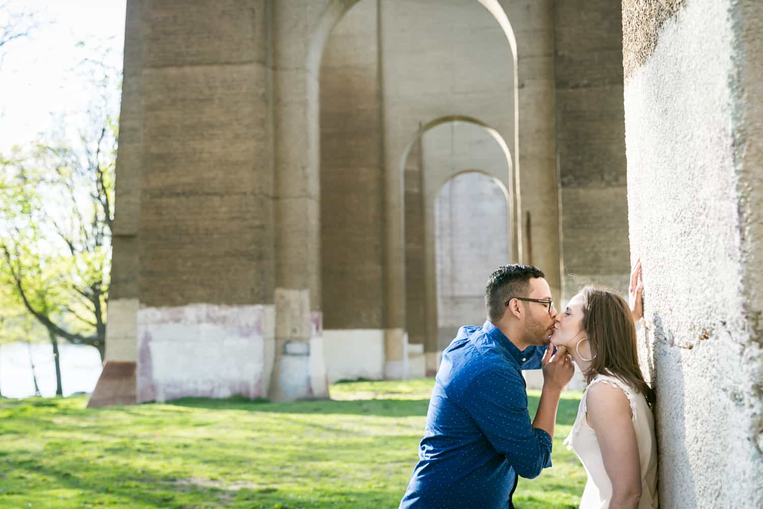 Couple kissing in front of stone arches during an Astoria Park engagement shoot