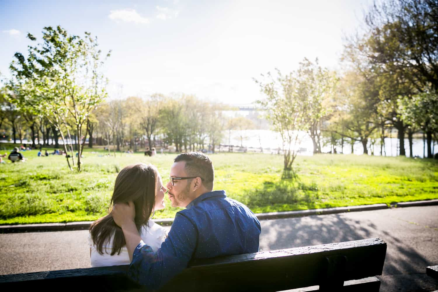 Couple kissing on bench during an Astoria Park engagement shoot