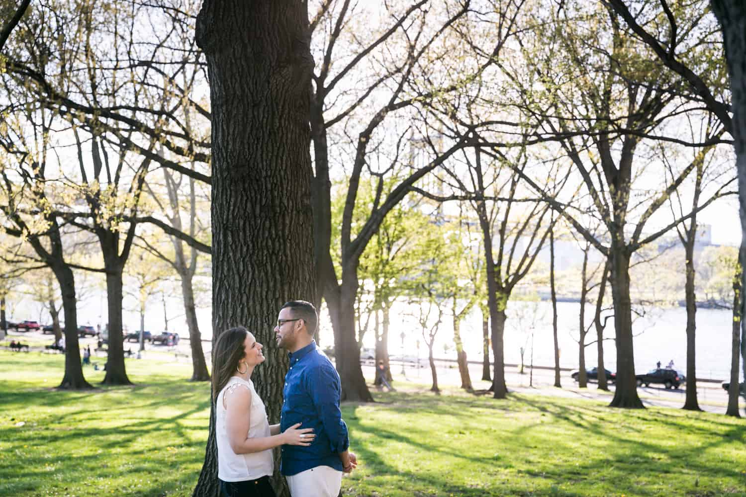 Couple hugging in front of tree during an Astoria Park engagement shoot