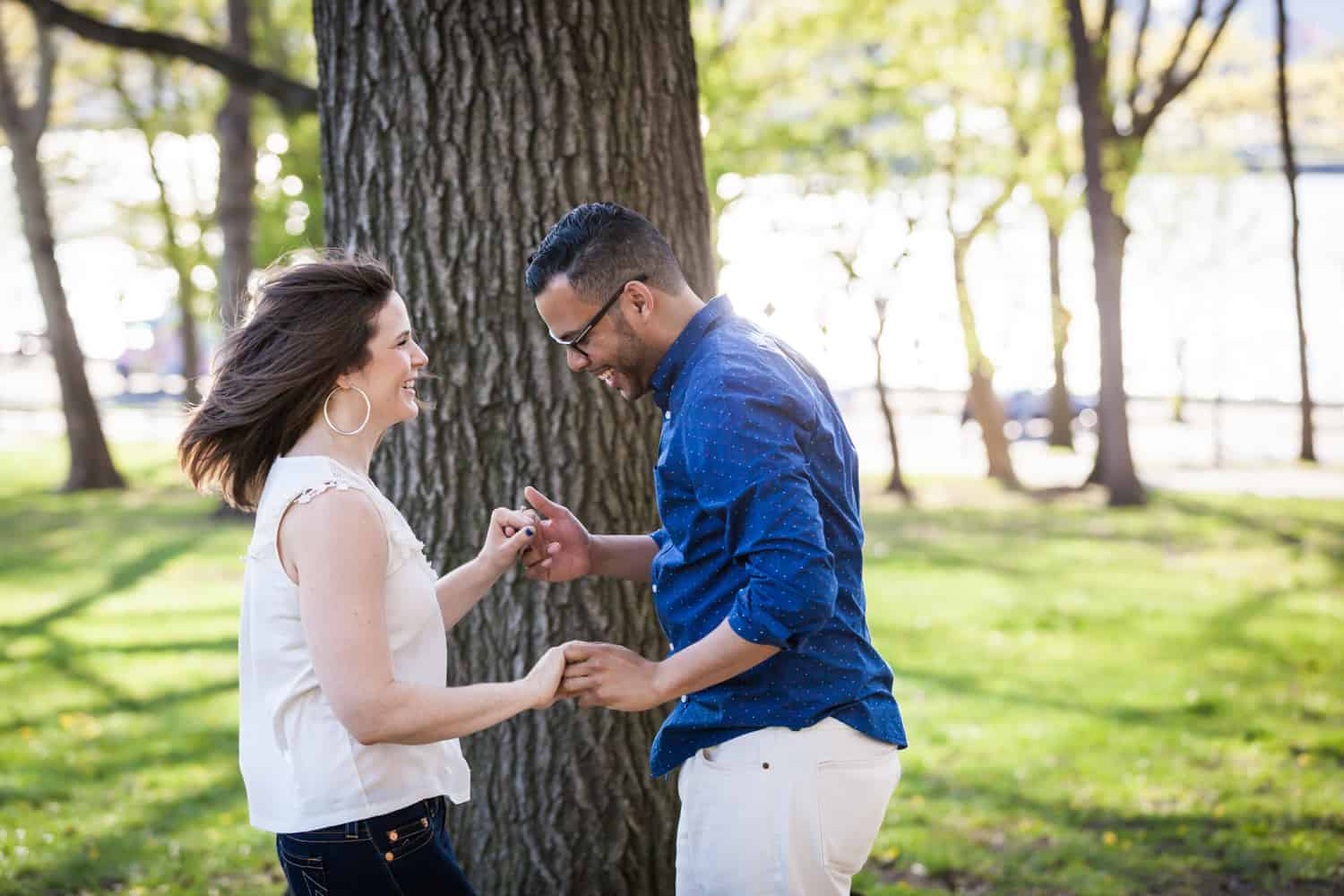 Couple dancing in front of tree during an Astoria Park engagement shoot