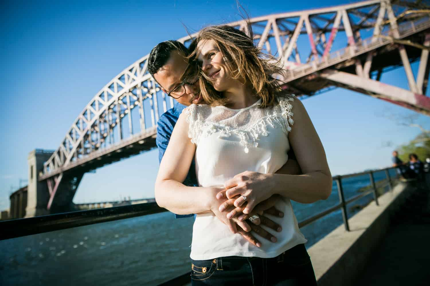 Couple hugging in front of Hellgate Bridge during an Astoria Park engagement shoot