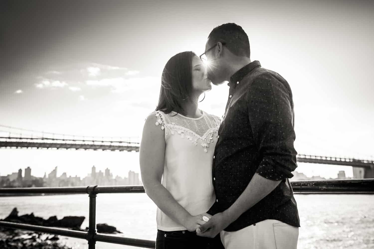 Black and white photo of couple kissing with sunlight in between