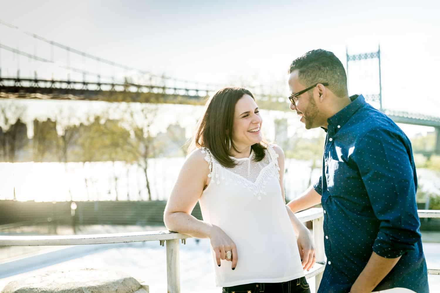 Couple leaning against railing during an Astoria Park engagement shoot