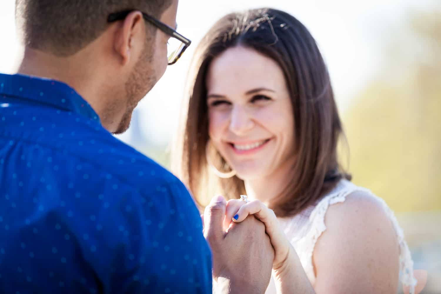 Woman showing engagement ring to man during an Astoria Park engagement shoot
