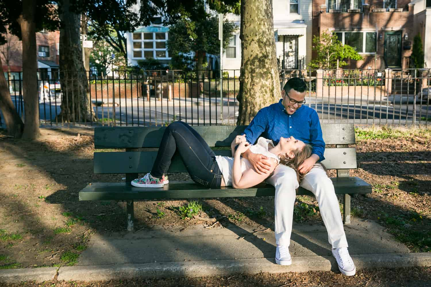 Woman lying in man's lap on bench during an Astoria Park engagement shoot