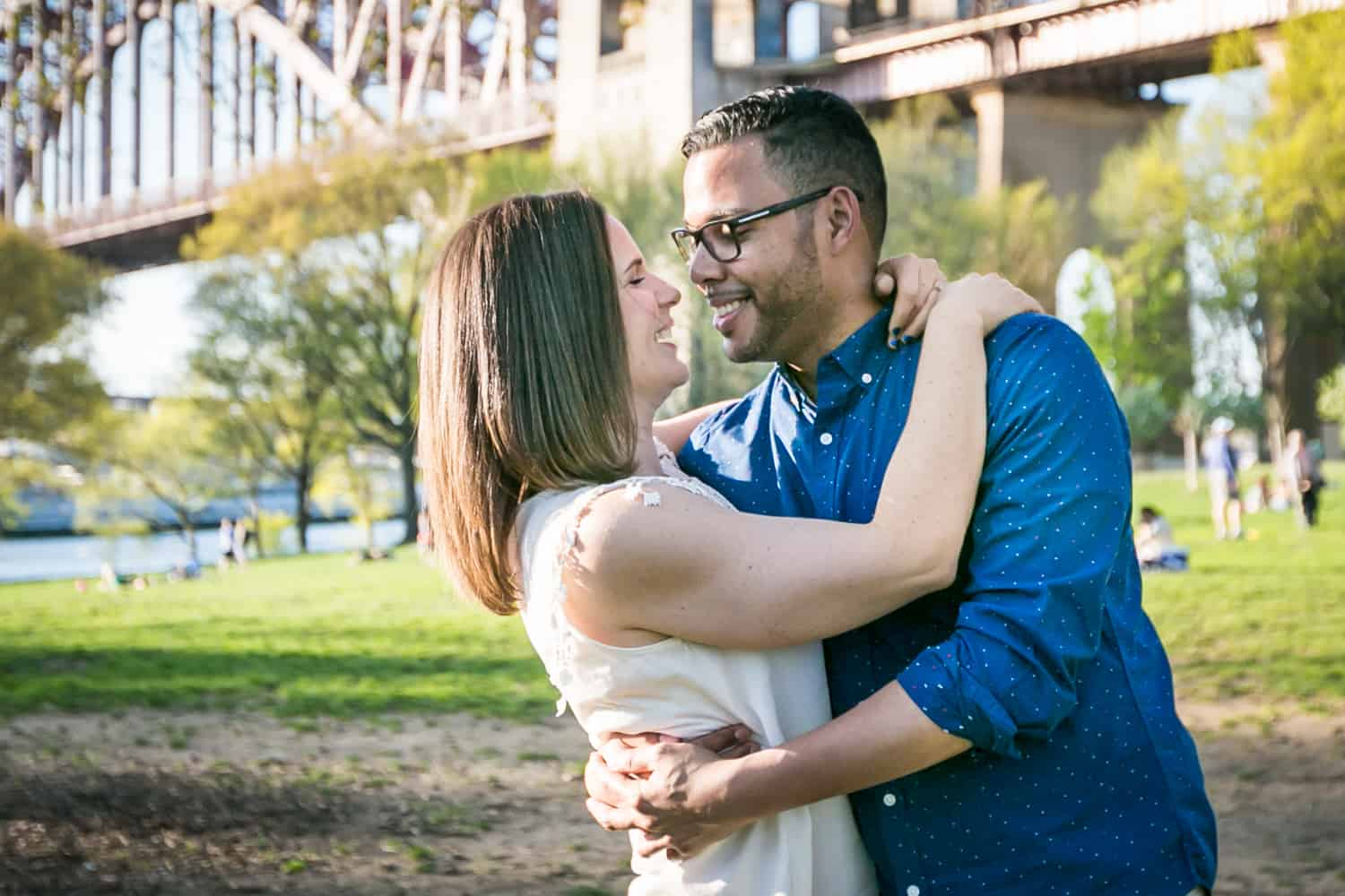 Couple dancing in front of Hellgate Bridge during an Astoria Park engagement shoot