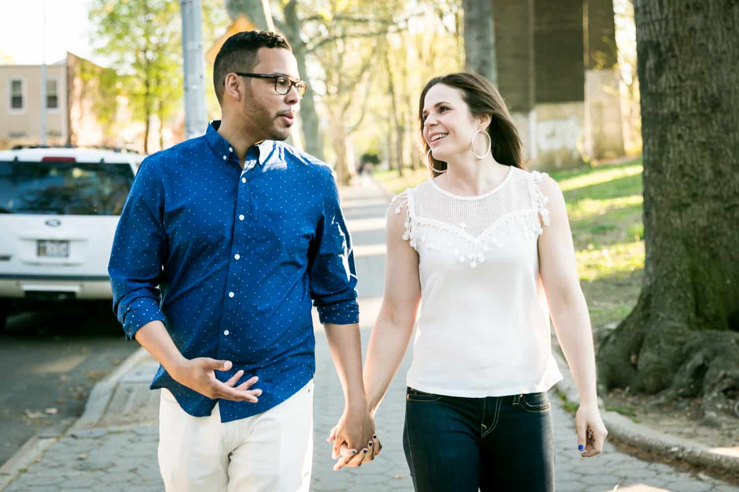 Couple walking hand-in-hand during an Astoria Park engagement shoot