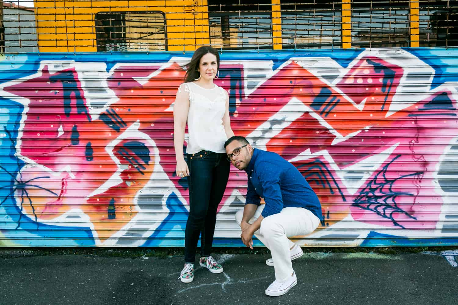 Couple in front of colorful graffiti during an Astoria Park engagement shoot