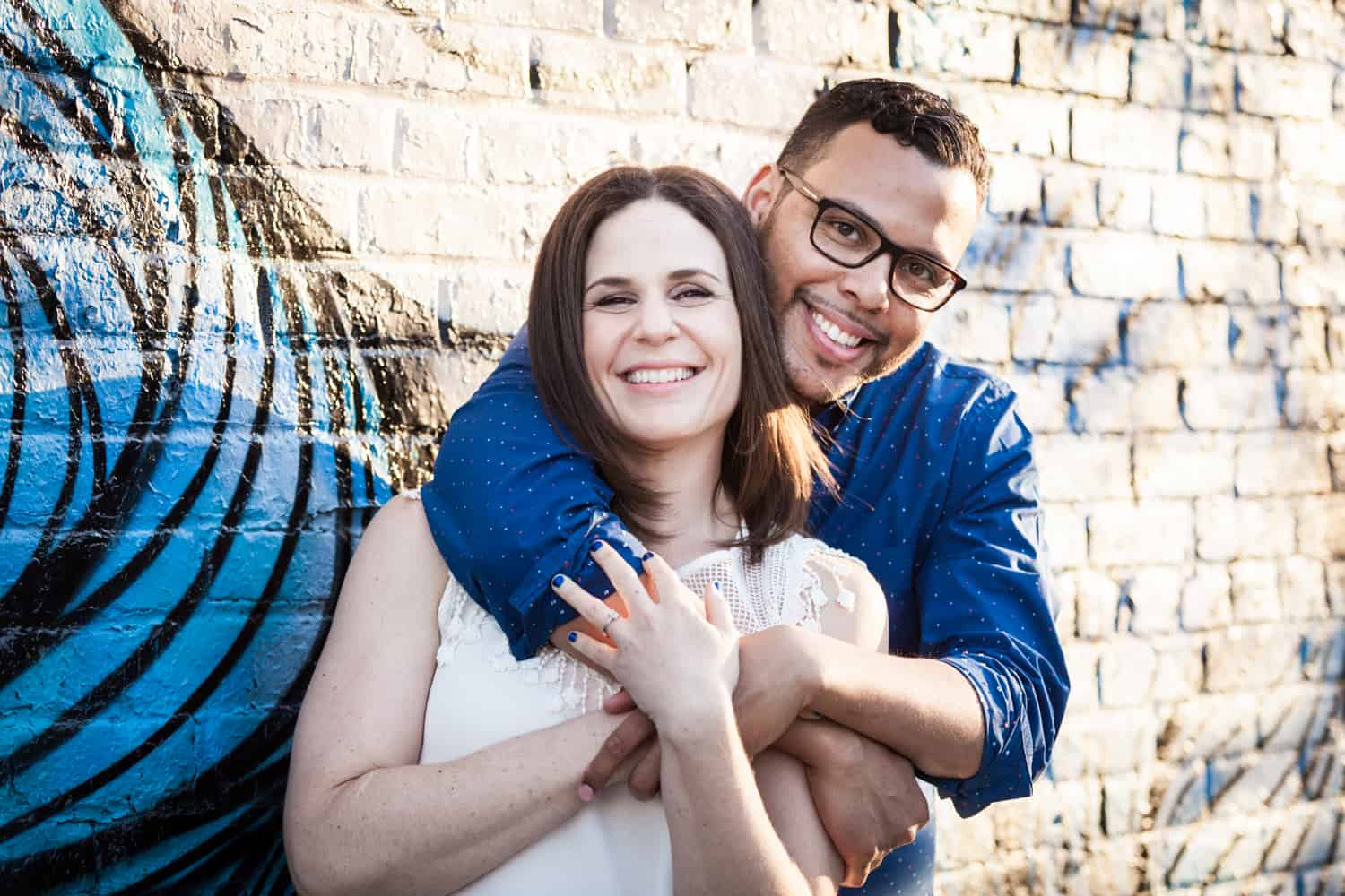 Man hugging woman from behind in front of brick wall