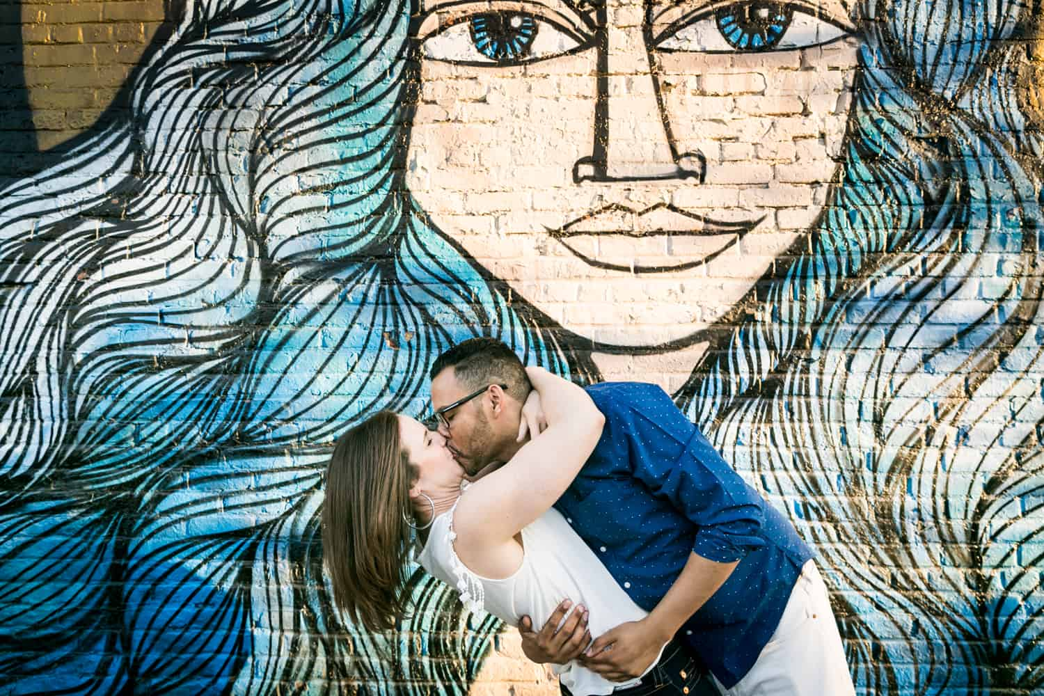 Couple kissing in front of graffiti
