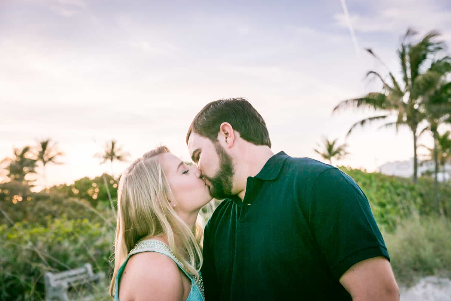 Couple kissing in front of beach during a Coral Cove Park engagement shoot