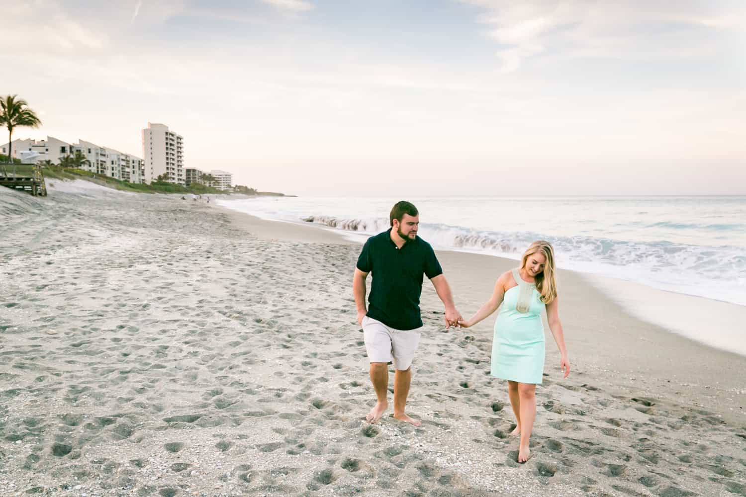 Couple holding hands and walking on beach during a Coral Cove Park engagement shoot