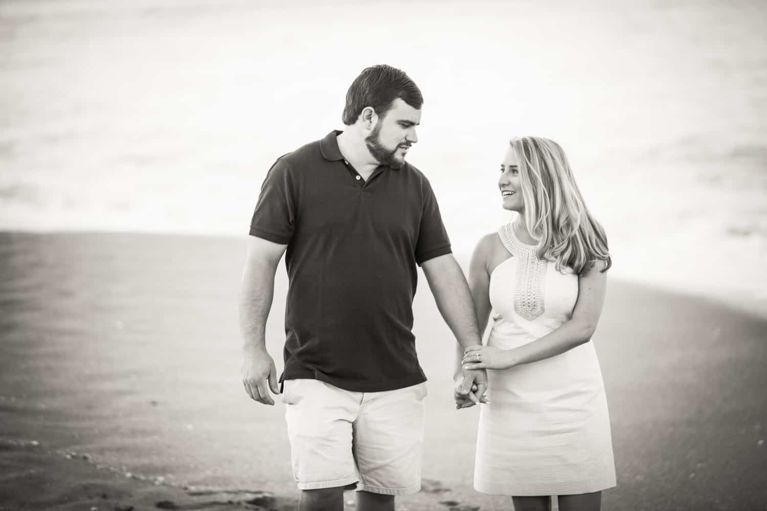 Black and white photo of couple holding hands on beach during a Coral Cove Park engagement shoot