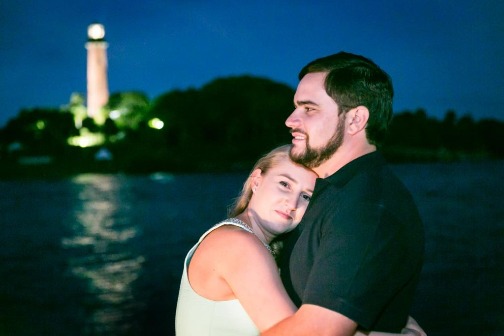 Couple hugging at night with lighthouse in background during a Coral Cove Park engagement shoot