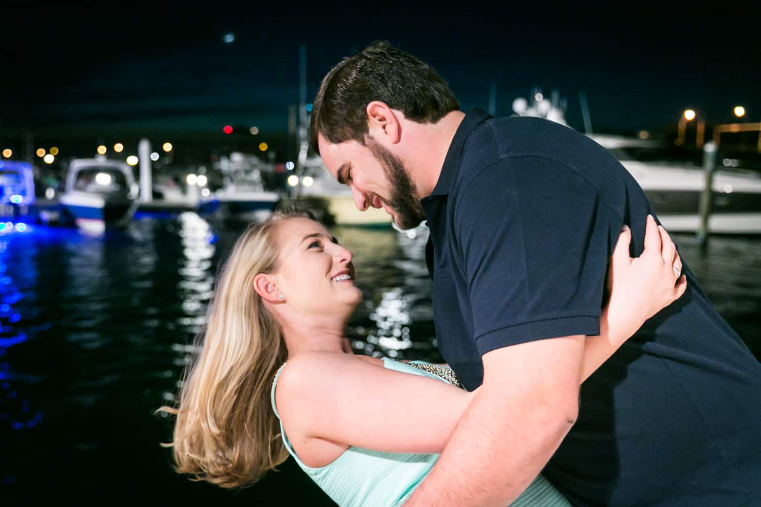 Couple dancing in front of water at night during a Coral Cove Park engagement shoot