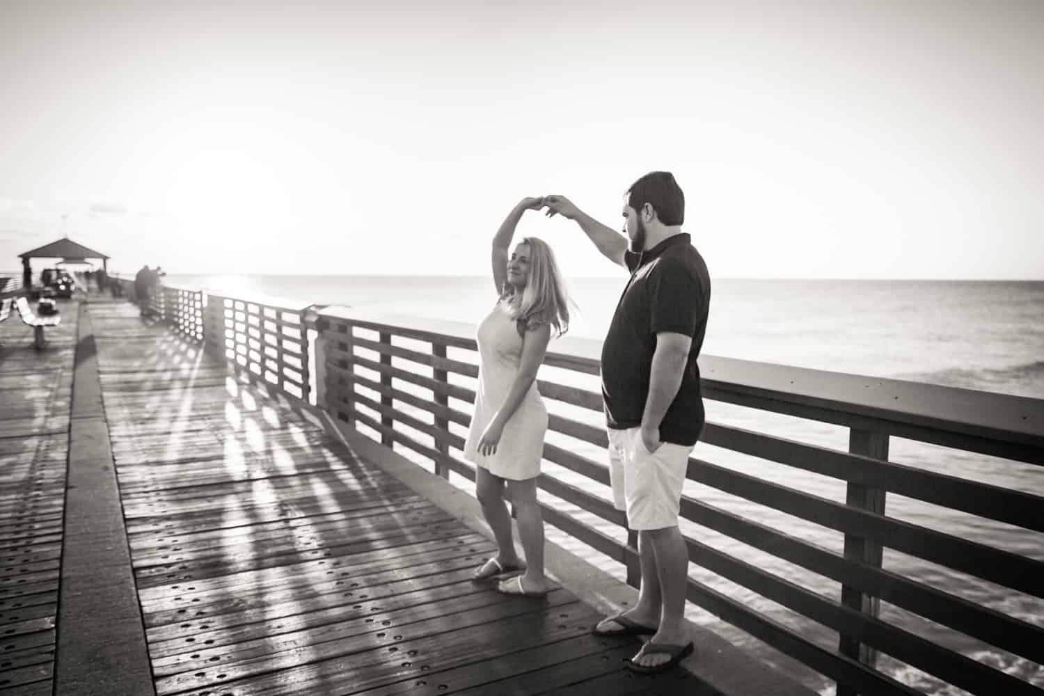 Black and white photo of couple dancing on dock