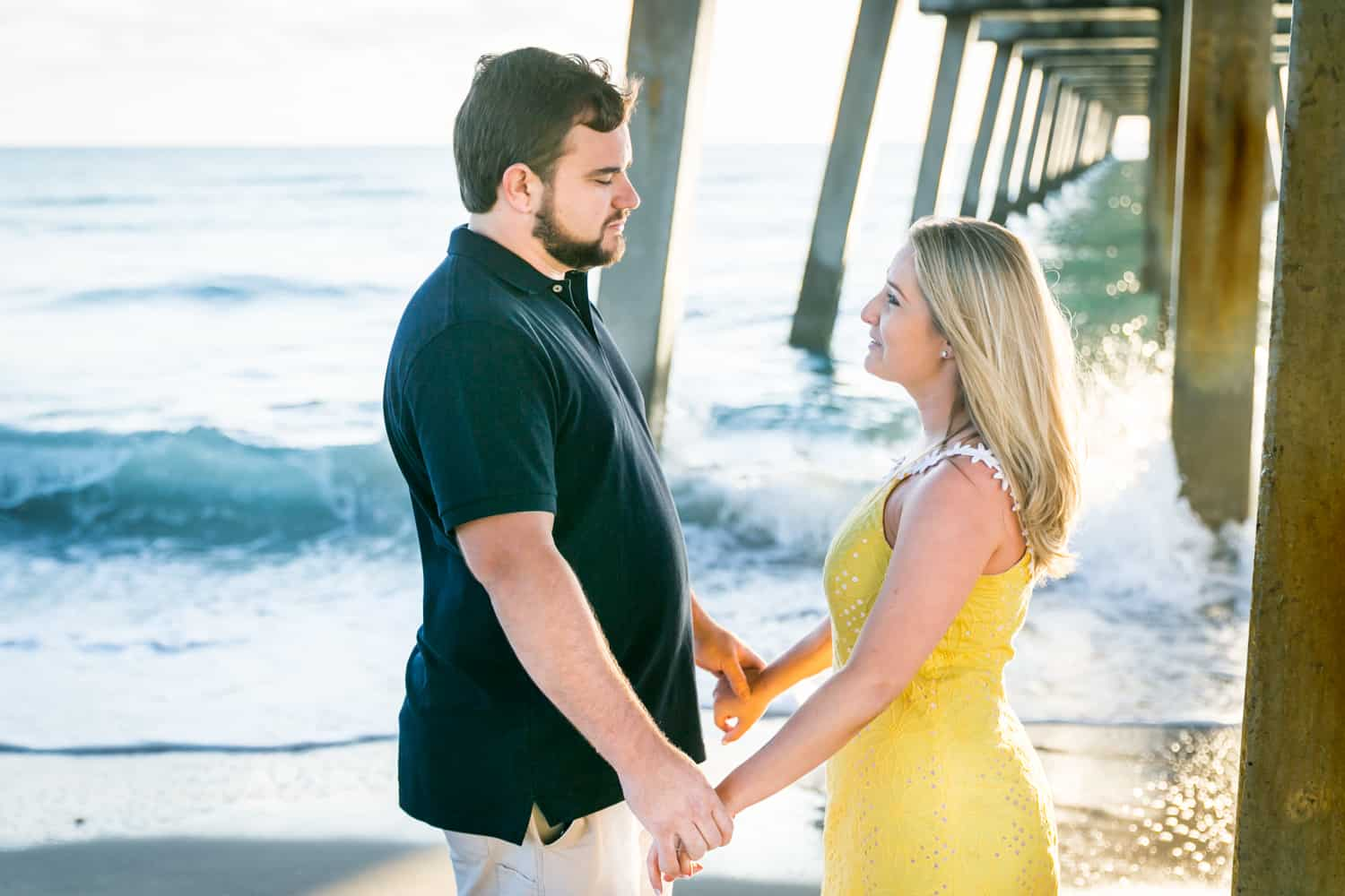 Couple holding hands under dock during a Coral Cove Park engagement shoot