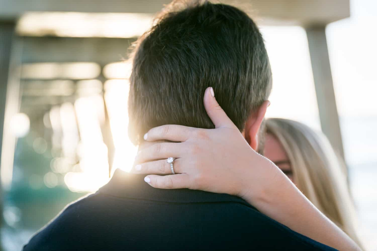 Woman's hand with engagement ring on back of man's head