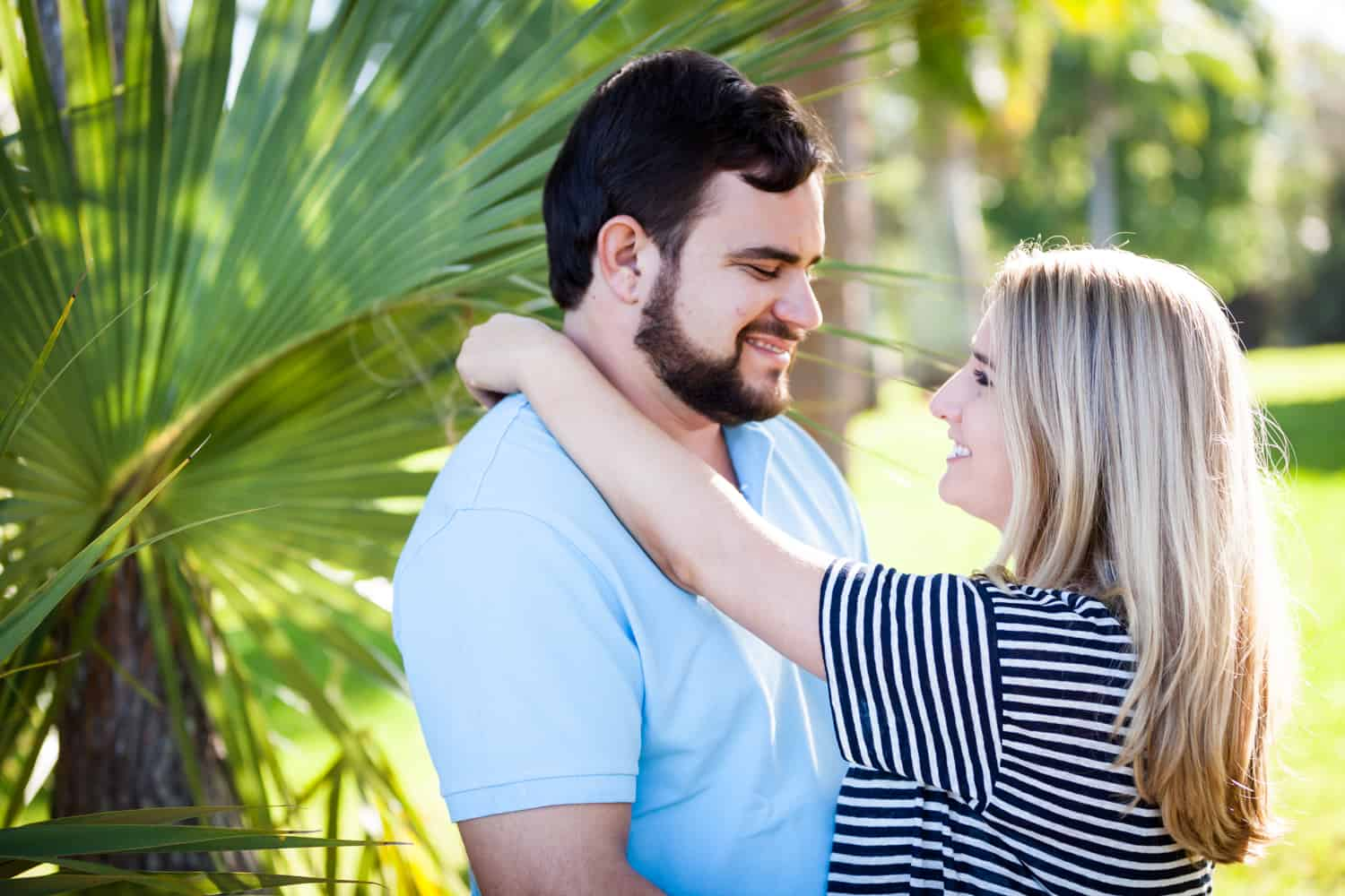 Couple hugging in front of palm frond