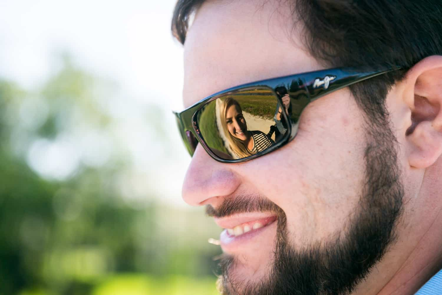 Woman reflected in man's sunglasses