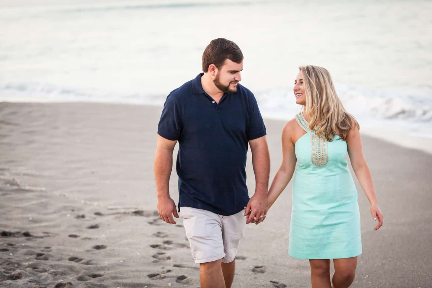 Couple holding hands on beach during a Coral Cove Park engagement shoot