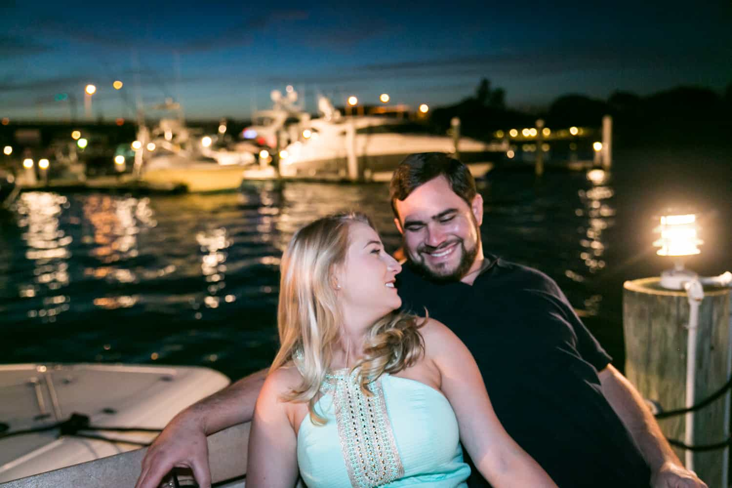 Couple on bench at night overlooking water during a Coral Cove Park engagement shoot