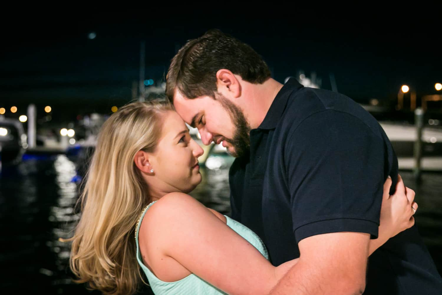 Couple touching foreheads at night during a Coral Cove Park engagement shoot