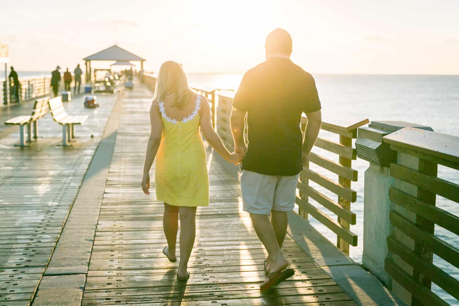 Couple holding hands and walking on pier during a Coral Cove Park engagement shoot