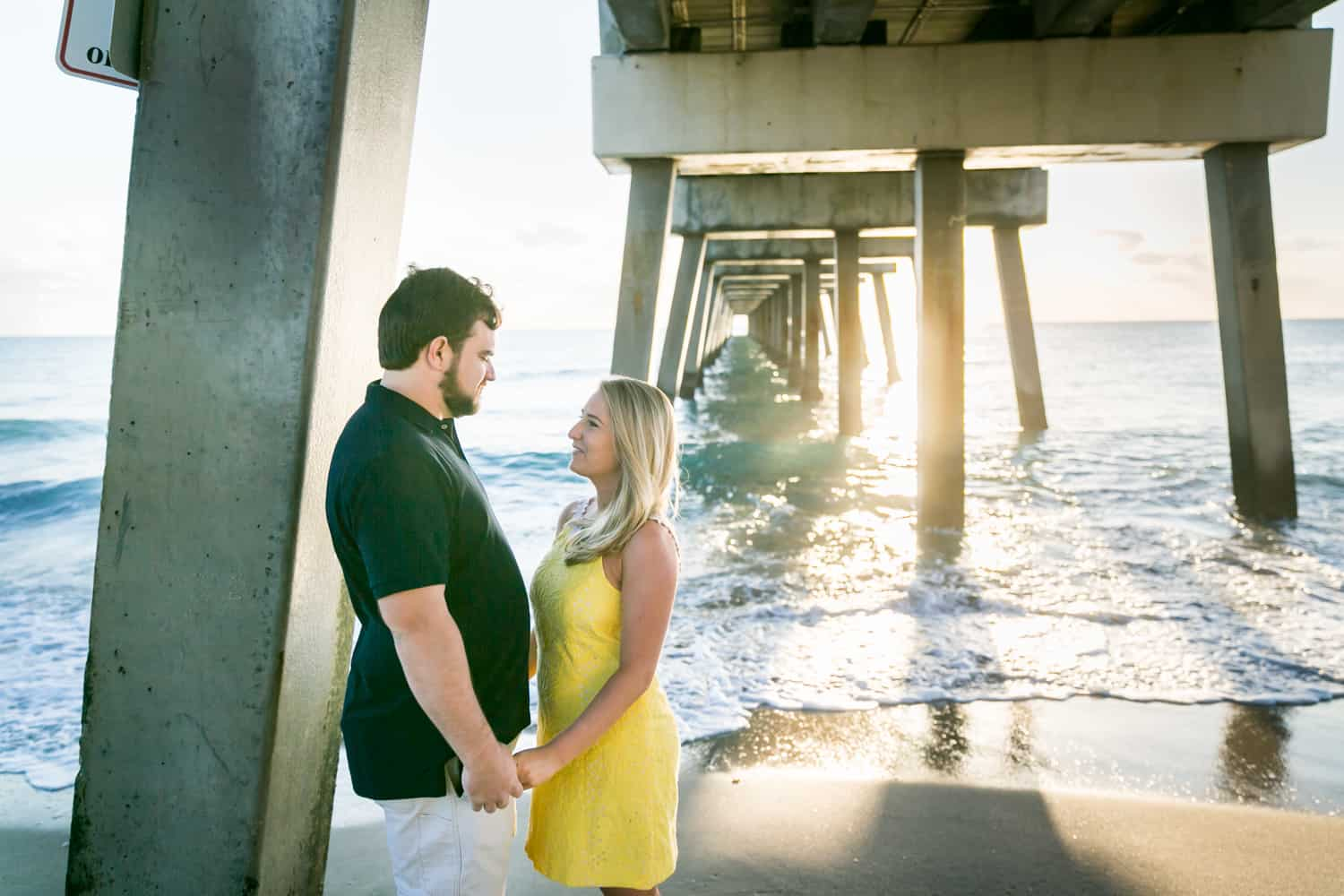 Couple holding hands under pier