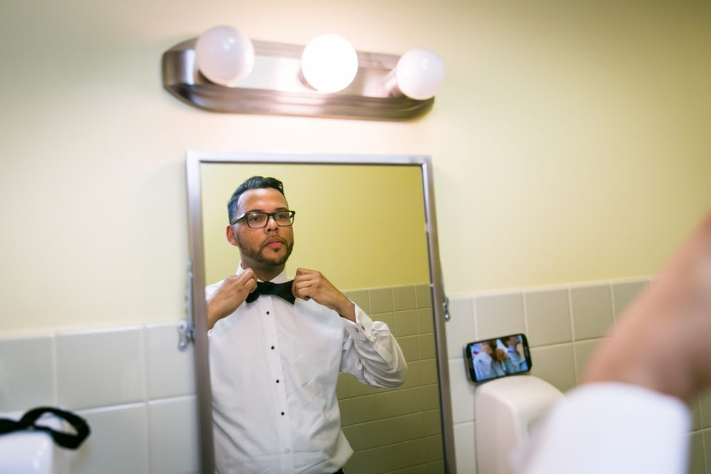 Groom adjusting bow tie in mirror before wedding