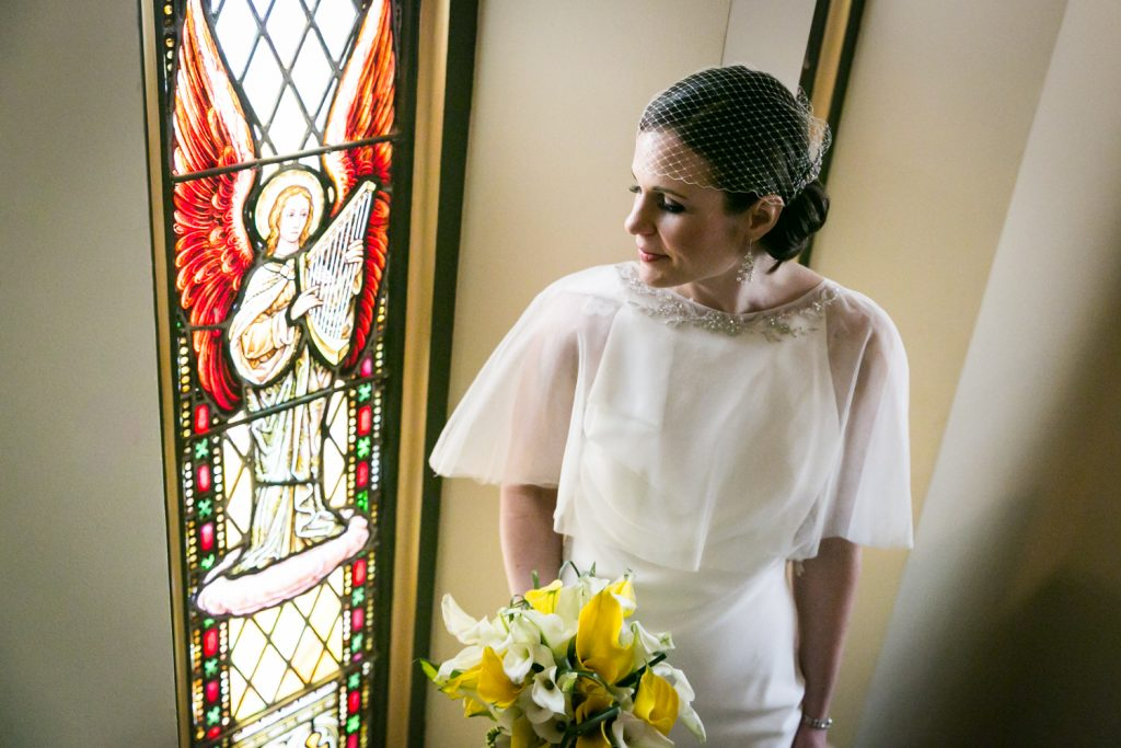 Bride with bouquet looking at stained glass window