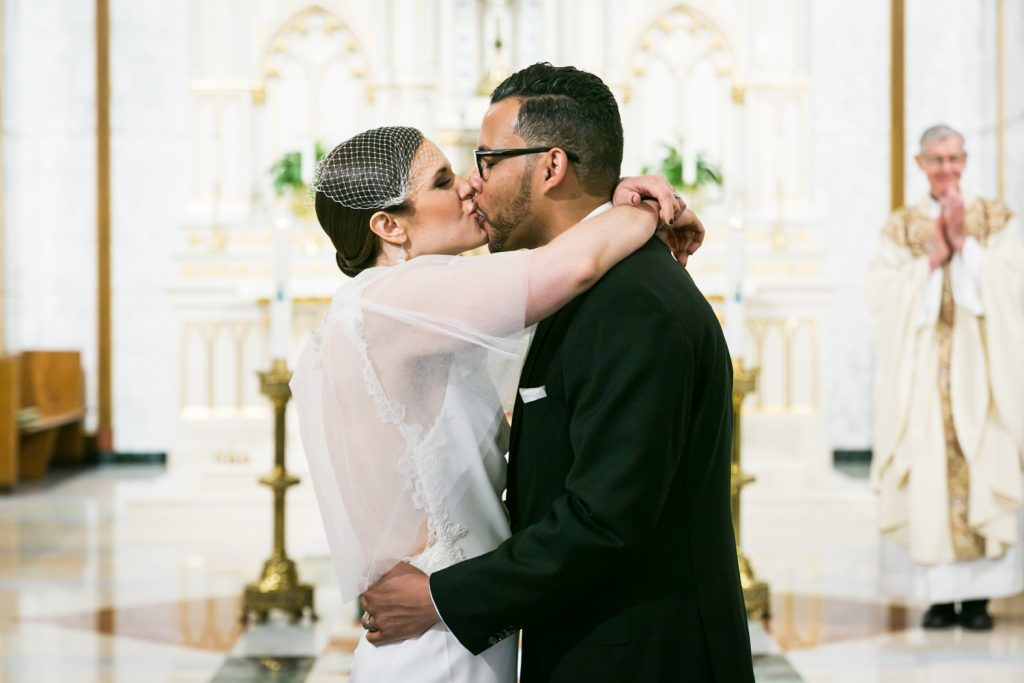 Bride and groom kissing after Our Lady of Mt. Carmel Church wedding ceremony