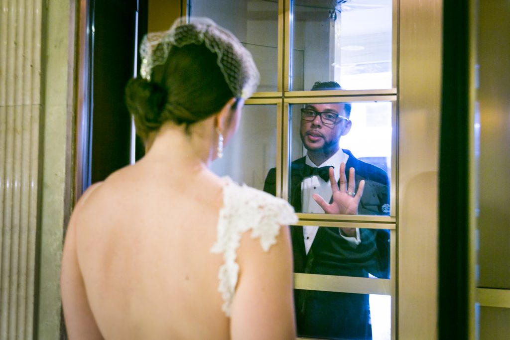 Bride looking at groom through turnstile door in Roosevelt Hotel wedding photo
