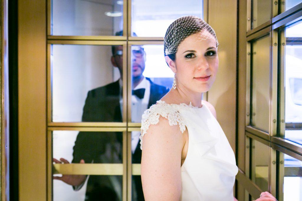 Bride with groom behind turnstile door in Roosevelt Hotel wedding photo