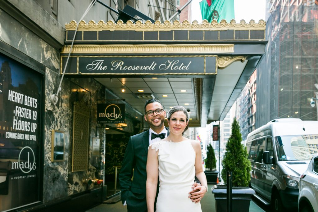 Bride and groom outside hotel entrance in Roosevelt Hotel wedding photo