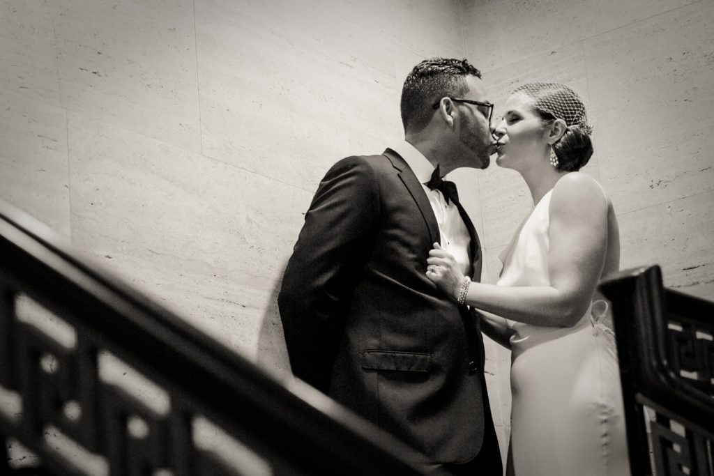 Black and white photo of bride and groom kissing in stairwell in Roosevelt Hotel wedding photo