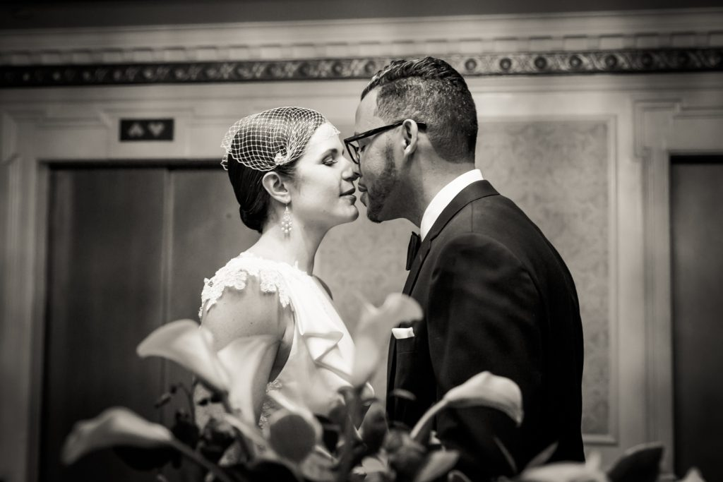 Black and white photo of bride and groom about to kiss across plant in Roosevelt Hotel wedding photo