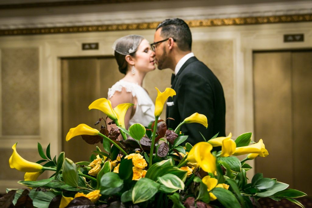 View through yellow plant of bride and groom about to kiss in Roosevelt Hotel wedding photo