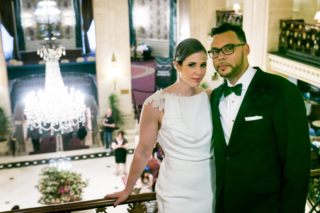 Bride and groom with hotel lobby in background in Roosevelt Hotel wedding photo