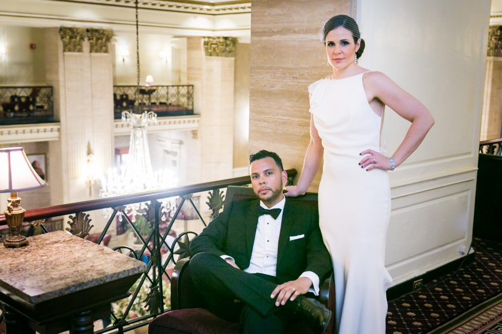 Bride standing above sitting groom in Roosevelt Hotel wedding photo