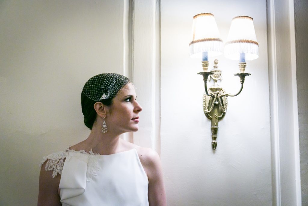 Bride looking at wall sconce in Roosevelt Hotel wedding photo