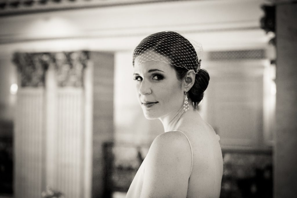 Black and white photo of bride looking over her shoulder in Roosevelt Hotel wedding photo