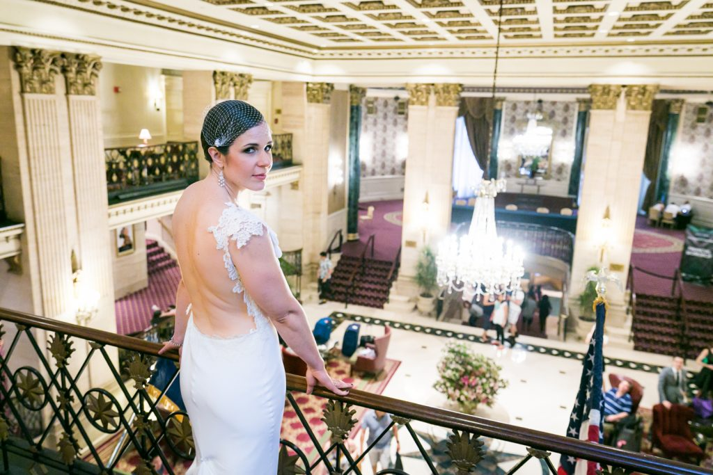 Bride looking back at camera with hotel lobby in background in Roosevelt Hotel wedding photo