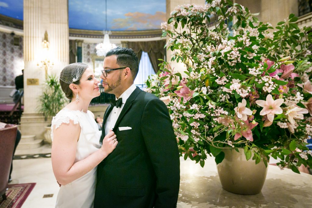 Bride pulling groom to her against table with flowers in Roosevelt Hotel wedding photo