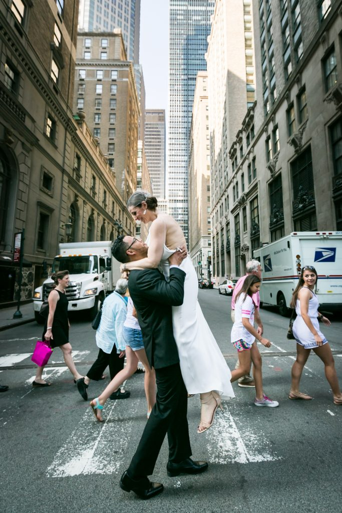 Groom lifting up bride in Manhattan crosswalk