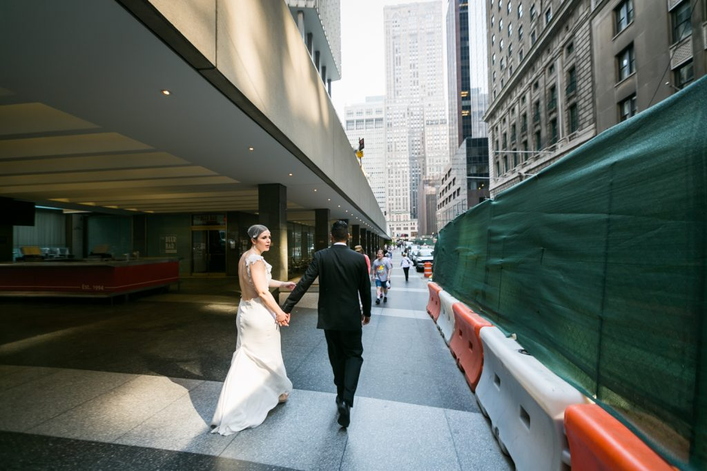 Groom leading bride down sidewalk outside Grand Central Terminal